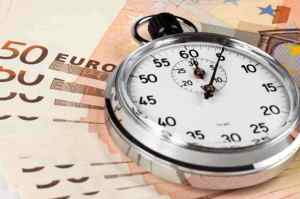 silver color old stopwatch on top of 50 euro banknotes