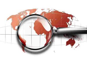 magnifying glass on red abstract world map